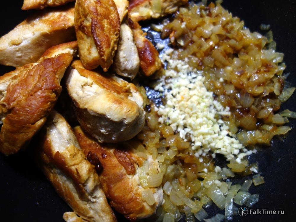 Сдвиньте курицу в сторону и обжарьте лук с чесноком
